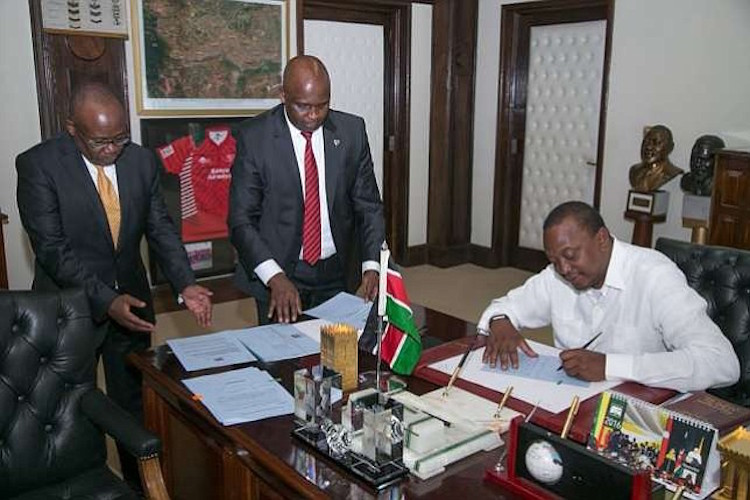 Photo: President Kenyatta signing commutations. Credit: International Scholarships.