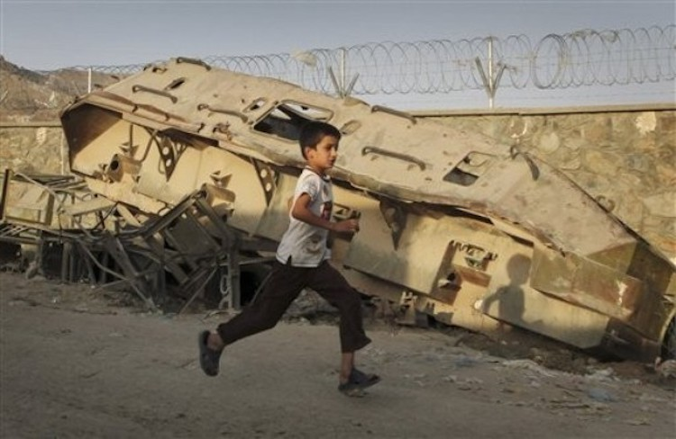 Photo: Debris of Afghan civil war: A boy runs past a destroyed Soviet-made armoured tank on a Kabul street, Afghanistan. (File photo)