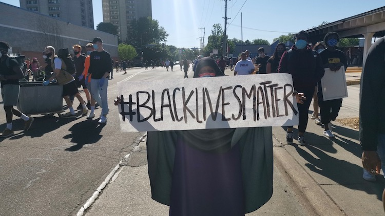 Photo: Woman on the streets of Minneapolis holds #BlackLivesMatter sign. Credit: Breakthrough News