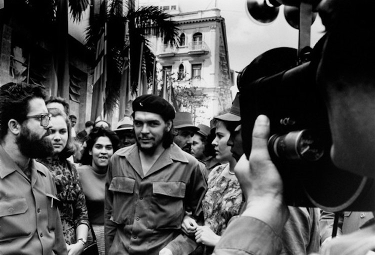 Photo (Public Domain): Cuban photographer Alberto Korda taking a picture of Che Guevara walking through a throng of cameramen down the streets in Havana, Cuba, with arms linked to his wife Aleida March in 1960.