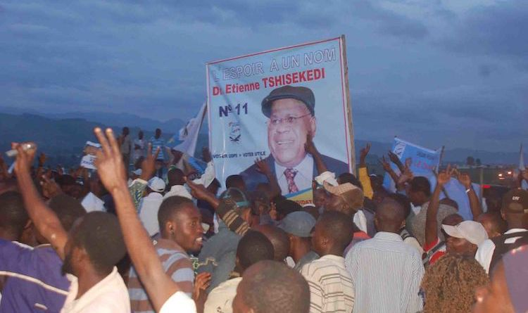 Photo: A crowd in the Democratic Republic of the Congo with people holding up a sign in support of Étienne Tshisekedi's presidential campaign in November 2011. Source: Wikimedia Commons | CC BY 2.0