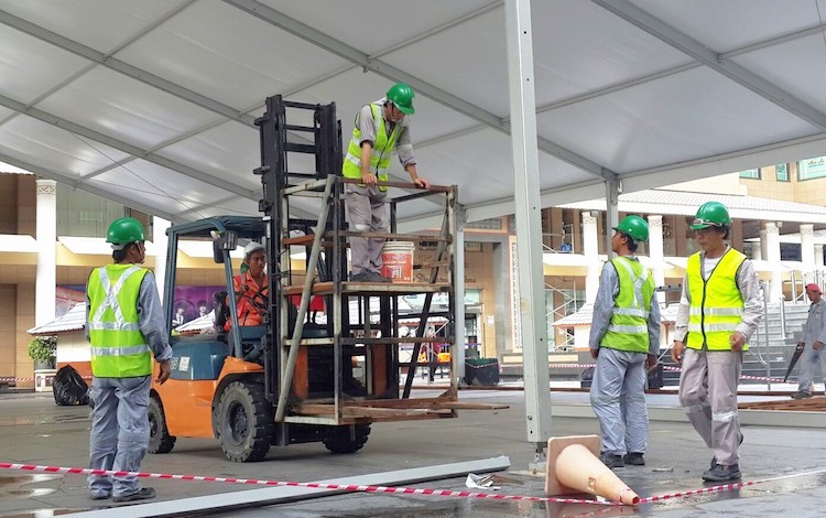 Photo: Philippine overseas workers assembling the tent for an event in the capital city of Brunei. Credit: jyppe.com CC BY-SA 3.0