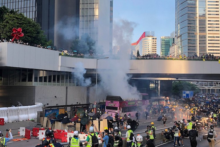 Photo: Police firing tear gas to disperse protesters near Central Government Complex on 5 August 2019. VOA Cantonese. Source: Wikimedia Commons.