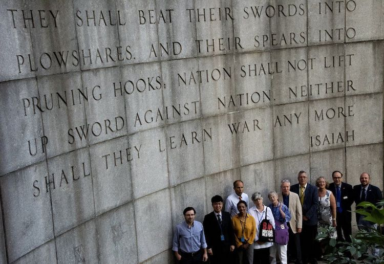 "Photo: Faith groups' representatives in front of the Isaiah Wall across the street from the United Nations Building in New York City with the Bible verse ""...they shall beat their swords into plowshares, and their spears into pruning hooks: Nation shall not lift up sword against nation, neither shall they learn war any more."" Credit: ICAN"