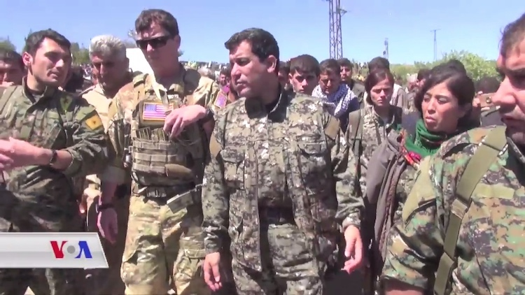 Photo: A US military officer and YPG and YPJ commanders tour an area hit by Turkish airstrikes in April 2017. YPG, the People's Protection Units, is a mainly-Kurdish militia in Syria and the primary component of the Democratic Federation of Northern Syria's Syrian Democratic Forces. YPJ, The YPJ is an acronym whose translation means Women's Protection Units. It is the all-female brigade of the YPG. Credit: Wikimedia Commons.