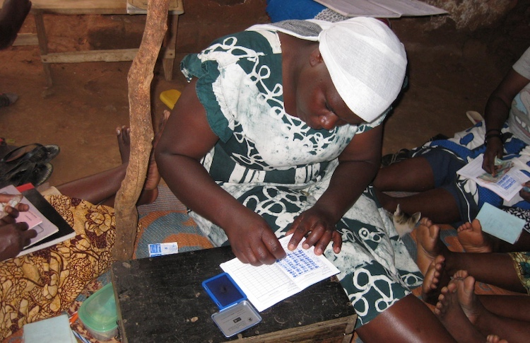 Photo: Zena Athumani, a member of the Kisanga Village Executive Committee, registering details of families which have qualified for the cash handouts as part of Social Safety Net Project run by TASAF. Credit: Edwin Mkendo