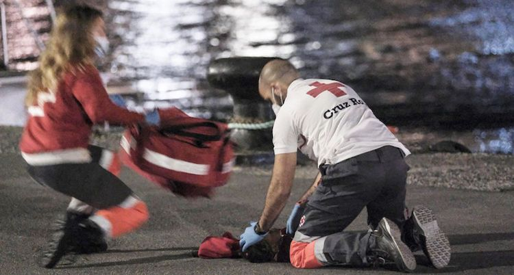 Photo: Two Red Cross workers racing to revive the child at the port of Arguineguín in Spain's Gran Canaria island. Source: El Pais | Ángel Medina G. / EFE