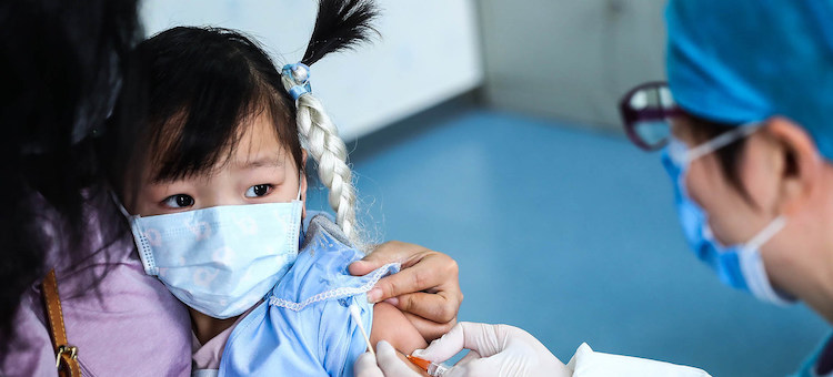 Photo: A three-year-old girl receives a vaccine shot at a community health centre in Beijing. Credit: UNICEF/Zhang Yuwei