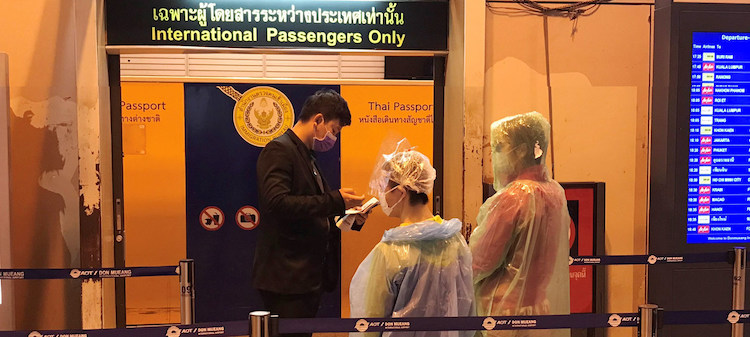 Photo: Passengers wearing face masks and disposable ponchos get their passports checked at Don Mueang International Airport in Bangkok, Thailand. UN News/Jing Zhang