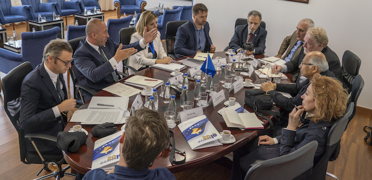 Photo: Prime Minister Ramush Haradinaj (second from left) talking to a media team end of June 2018 at his office in Pristina. He is flanked by Kosovo government officials. Credit: Cia Pak | Scannews.